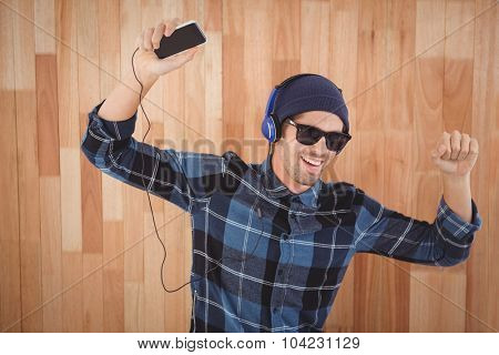 Happy hipster wearing headphones enjoying music against wooden wall