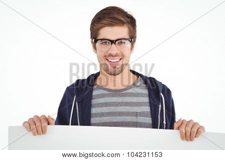 Portrait of man wearing eye glasses holding billboard against white background