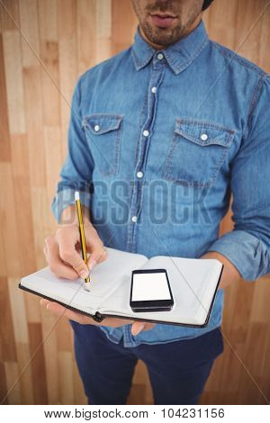 Mid section of man with mobile phone writing on book against wooden wall