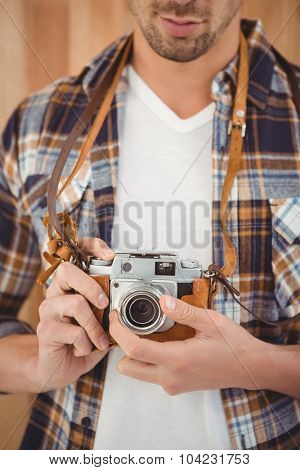 Mid section of hipster adjusting camera lens against wooden wall in office