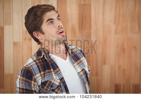 Surprised hipster looking up against wooden wall in office