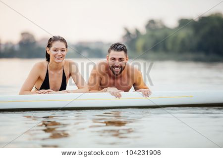 Man And Woman Relaxing In Water On A Paddleboard
