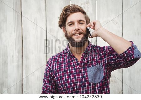 Portrait of hipster using mobile phone standing against wooden wall