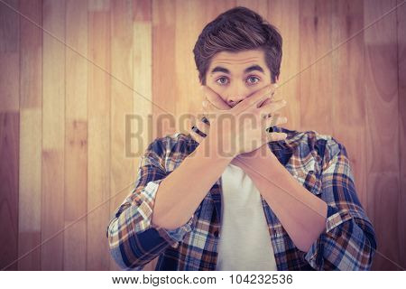 Portrait of shocked man covering mouth against wooden wall
