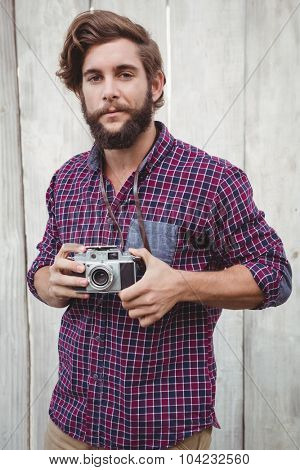 Portrait of confident hipster using camera against wooden fence