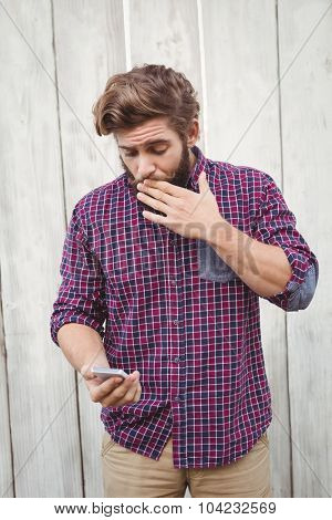 Shocked hipster looking at mobile against wooden wall