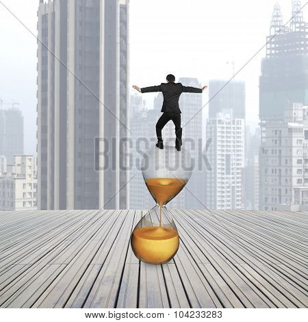 Rear View Of Businessman Balancing On Hourglass