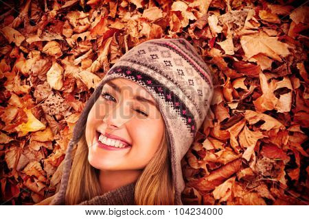 Happy blonde in winter clothes posing against autumn leaves on the ground