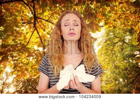 Sick blonde woman holding paper tissue against branches and autumnal leaves against the sunlight