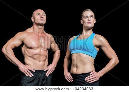 Muscular man and woman with hand on hip looking up against black background
