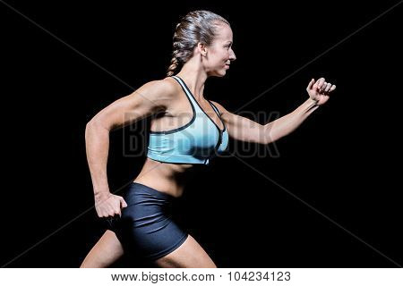 Side view of female athlete running against black background