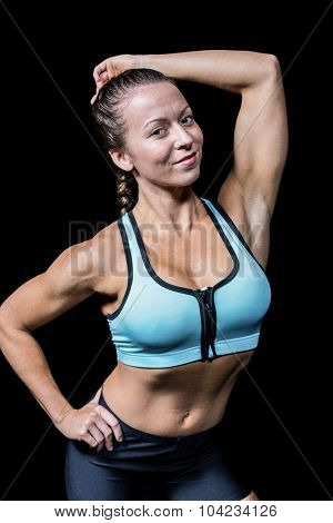 Portrait of fit smiling woman against black abckground