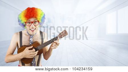Geeky hipster in afro rainbow wig playing guitar against city scene in a room