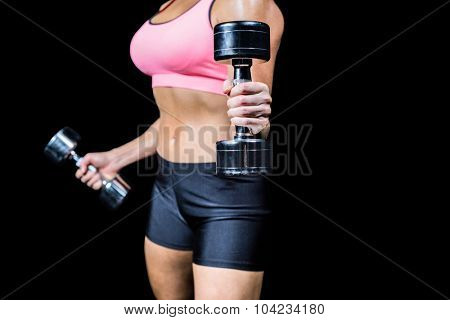 Close-up of dumbbells by slim woman exercising against black background