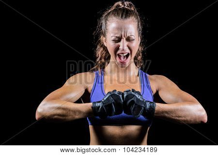 Aggressive female boxer flexing muscles against black background