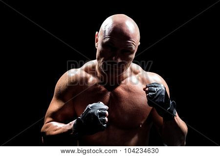 Shadow falling on confident fighter against black background