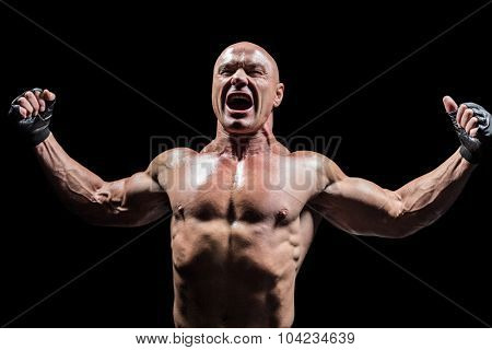 Angry fighter with arms outstretched against black background