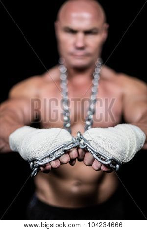 Portrait of confident man with bandage and chain against black bakcground