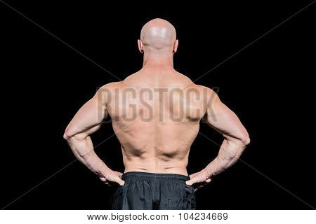 Rear view of confident bald man with hands on hip against black background