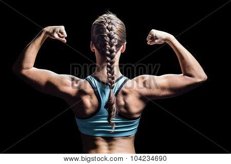 Rear view of woman with braided hair flexing muscles against black background