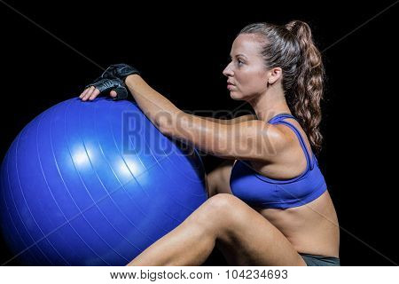 Side view of sporty woman with exercise ball against black background