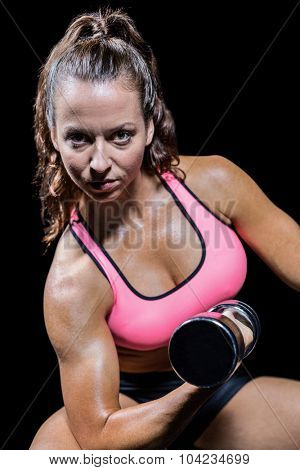 Portrait of confident fit woman lifting dumbbell against black background