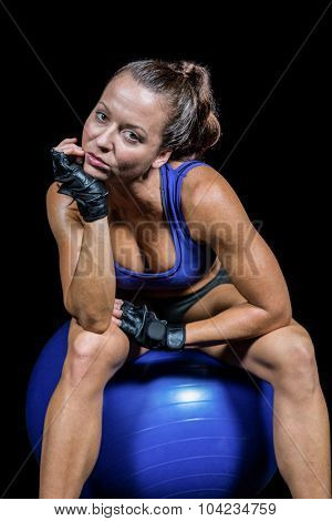 Portrait of fit woman sitting on exercise ball with hand on chin against black background