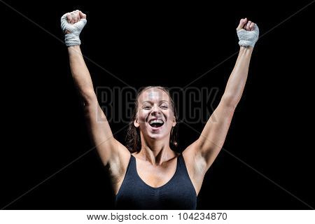 Happy winner with arms raised against black background