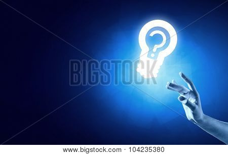 Close up of human hand touching with finger light bulb