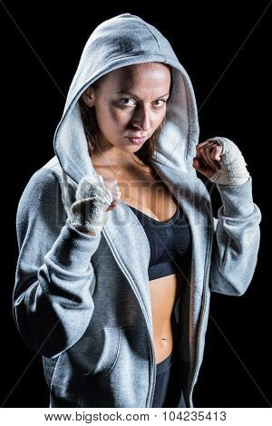 Portrait of female boxer in hood with fighting stance against black background