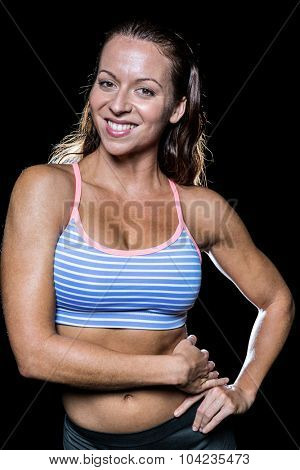 Portrait of smiling athlete with hands on hip against black background