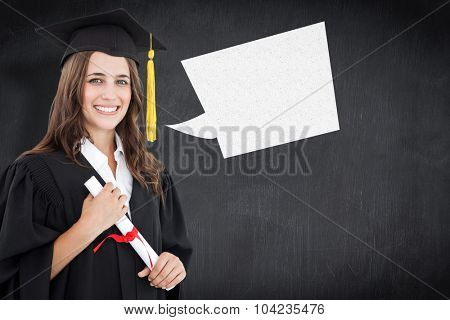 A smiling woman with a degree in hand as she looks at the camera against blackboard