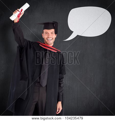 Smiling handsome boy showing his diploma to the camera against blackboard
