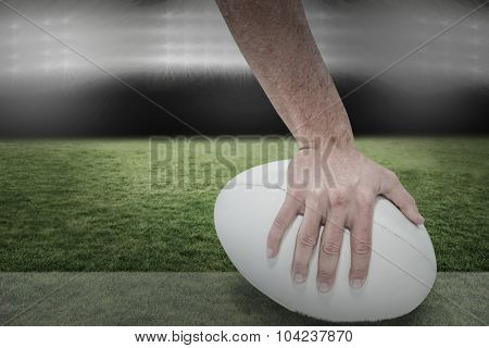 Close-up of sports player holding ball against spotlight