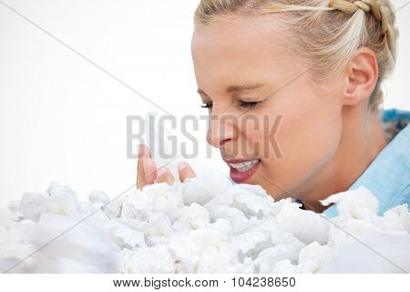 Ill woman sneezing into tissue against used tissues