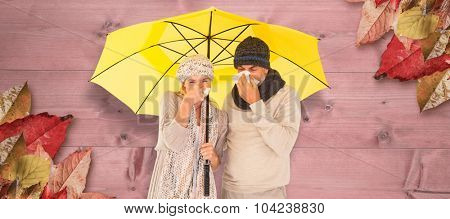 Couple sneezing in tissue while standing under umbrella against bleached wooden planks background
