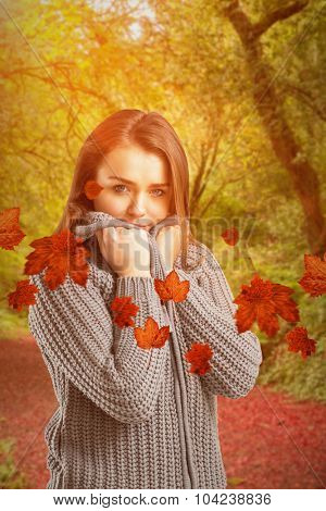 Pretty girl in winter jumper looking at camera against peaceful autumn scene in forest
