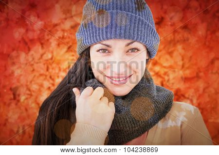 Attractive brunette looking at camera wearing warm clothes against peaceful autumn scene in forest