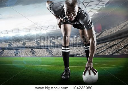 Portrait of rugby player smiling against rugby stadium