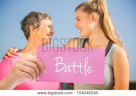 The word battle and hand holding card against sporty mother and daughter smiling at each other