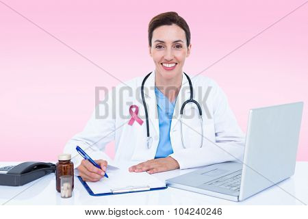 Portrait of smiling female doctor writing on pad against pink