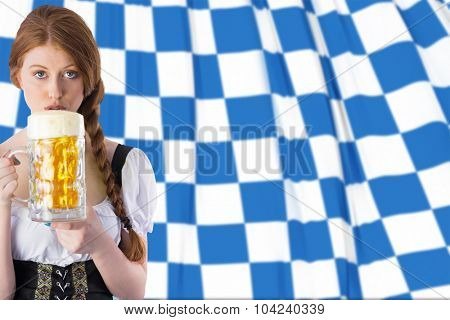 Oktoberfest girl drinking jug of beer against blue and white flag