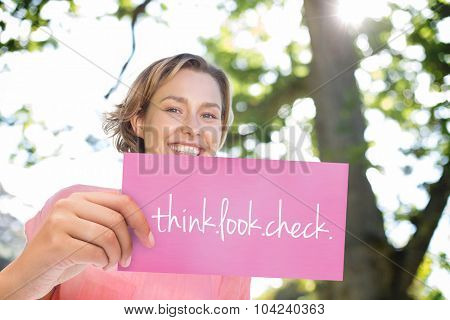 The word think.look.check. and hand holding card against smiling women running for breast cancer awareness