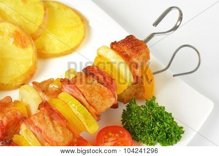 detail of marinated barbecue skewers with pork, vegetables and potatoes on white plate