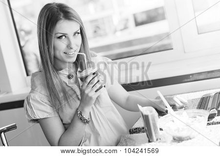 beautiful cheerful blond young woman drinking milkshake in cafe