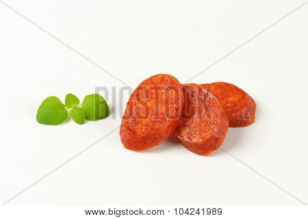 three slices of pepperoni sausage on white background