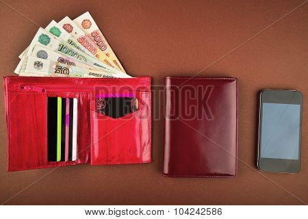Purse,money, Wallet And Phone On A Brown Background