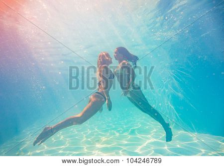 Two Young women swimming underwater in the swimming pool