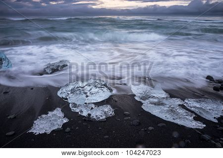 Blocks of ice from the glaciers break up and is washed ashore by the strong waves of the sea in Iceland.