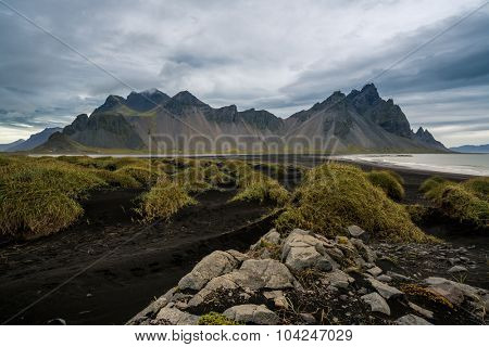 Mountains and volcanic lava sand dunes by the sea in Stokksness, Iceland.